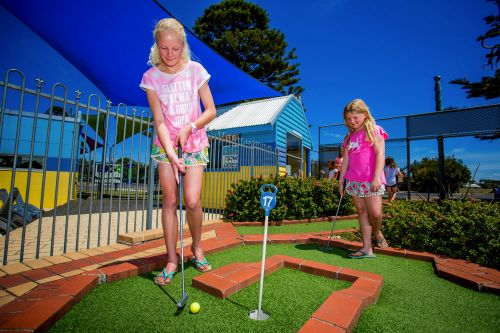 Two Girls Playing Mini Golf